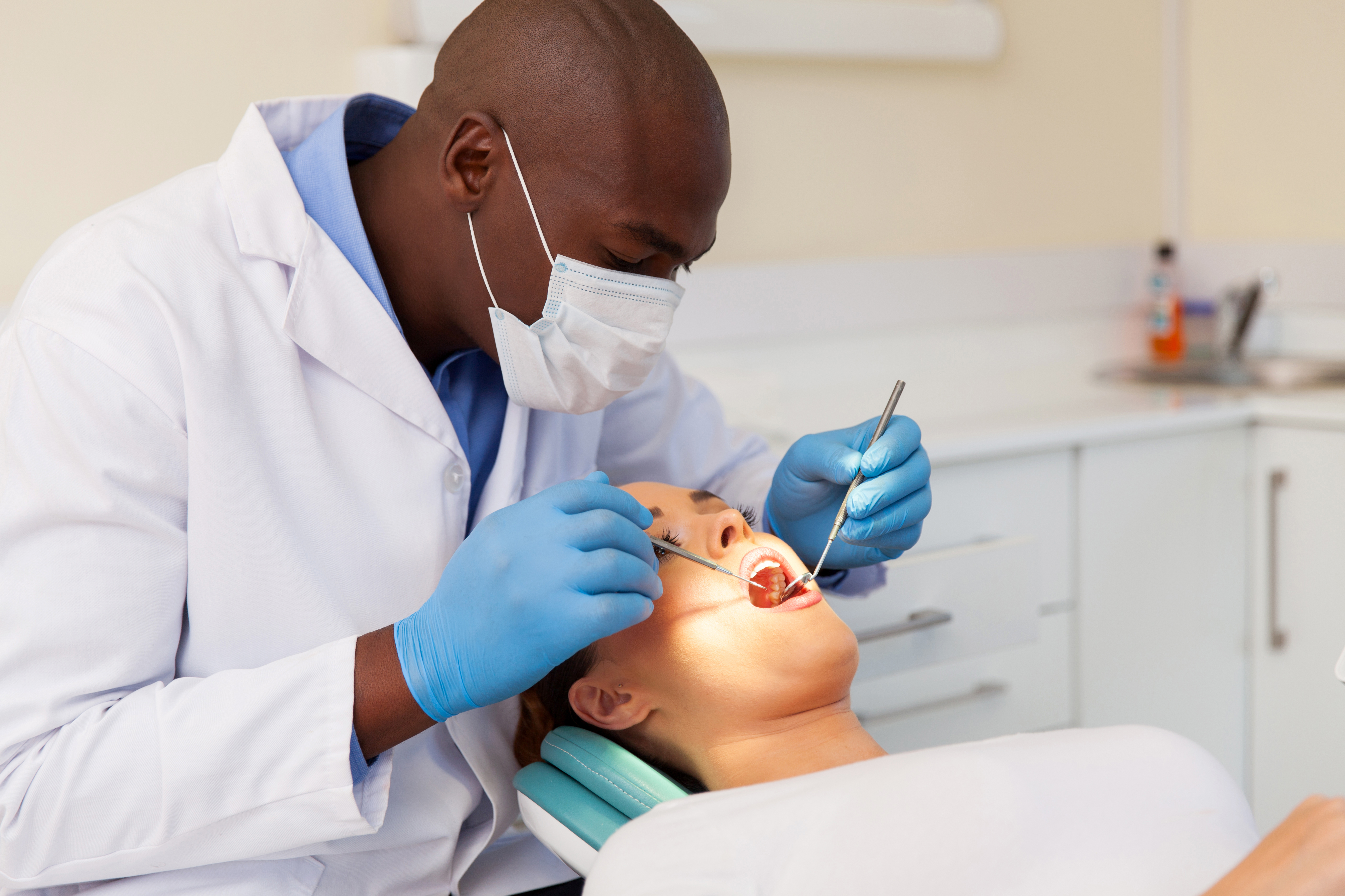 professional male dentist examining woman's teeth